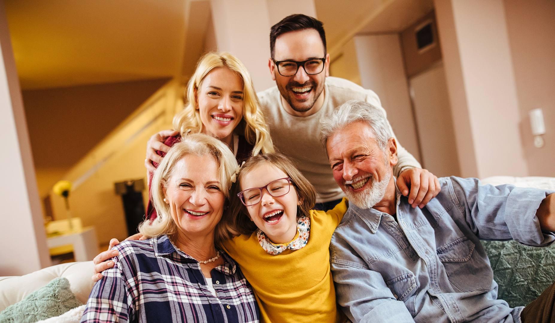 Szczęśliwa i spokojna o swoją przyszłość pięciosobowa rodzina uśmiecha się do zdjęcia