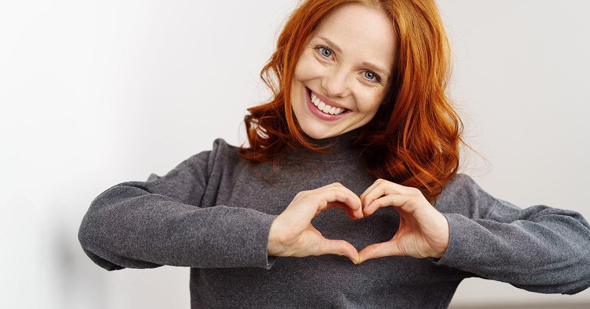 Uśmiechnięta rudowłosa kobieta pokazuje symbol serca ułożony z dłoni