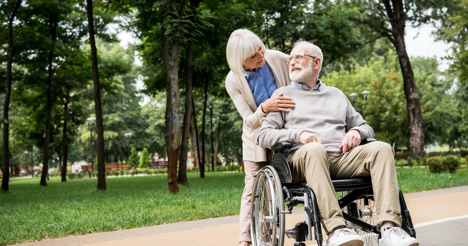 Starsza kobieta troszczy się o poruszającego się na wózku inwalidzkim mężczyznę