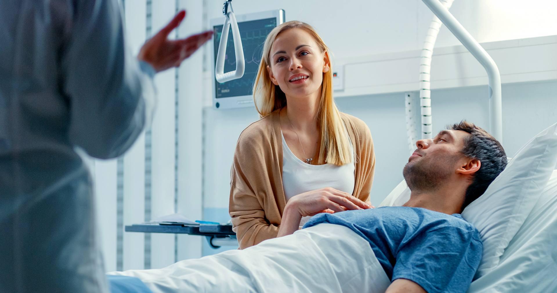 Kobieta z ulgą wysłuchuje lekarza, siedząc u boku hospitalizowanego mężczyzny