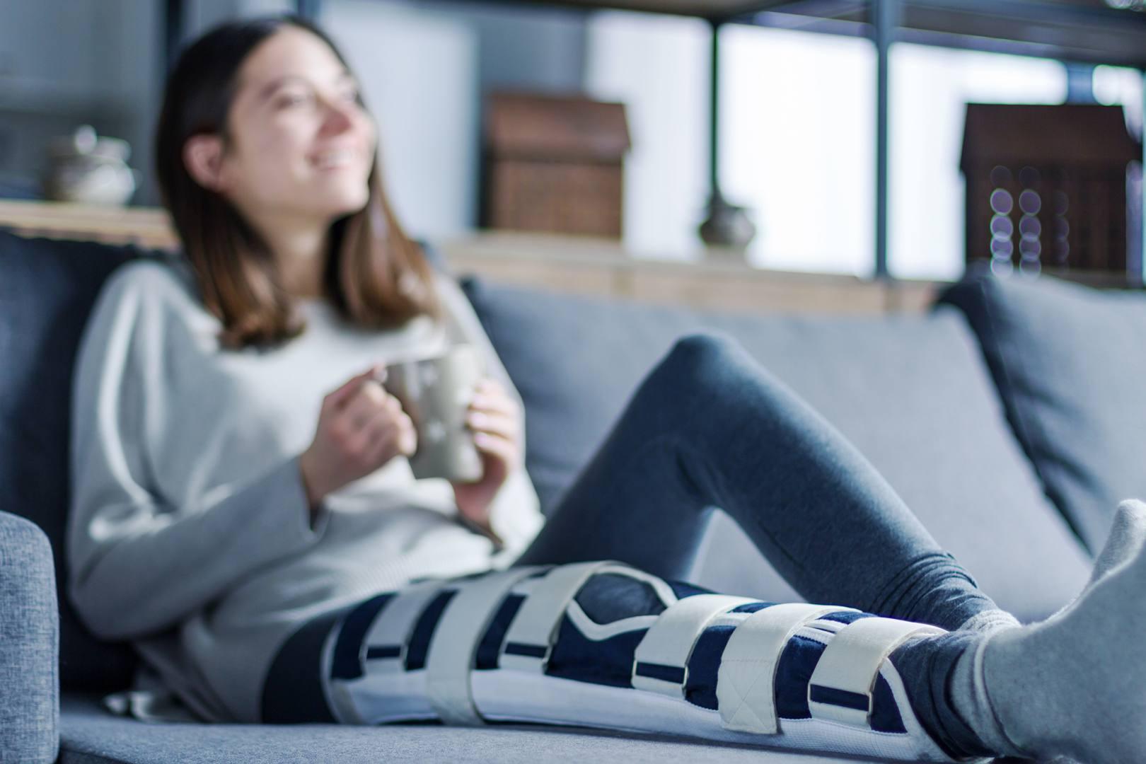 Ubezpieczona kobieta odpoczywa w domu, dając czas na regenerację kontuzjowanej nodze