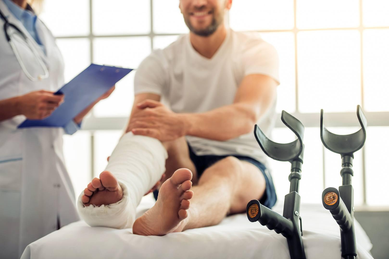 Ubezpieczony mężczyzna z nogą w gipsie siedzi na łóżku i słucha opinii lekarza