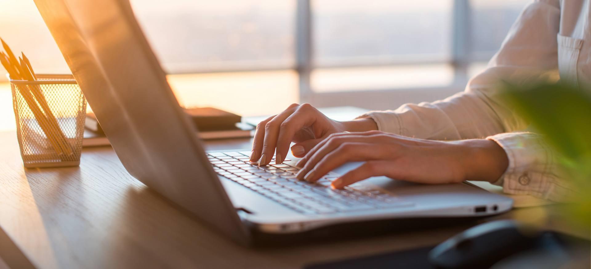 Kobieta wyszukuje na laptopie informacji o ubezpieczeniach