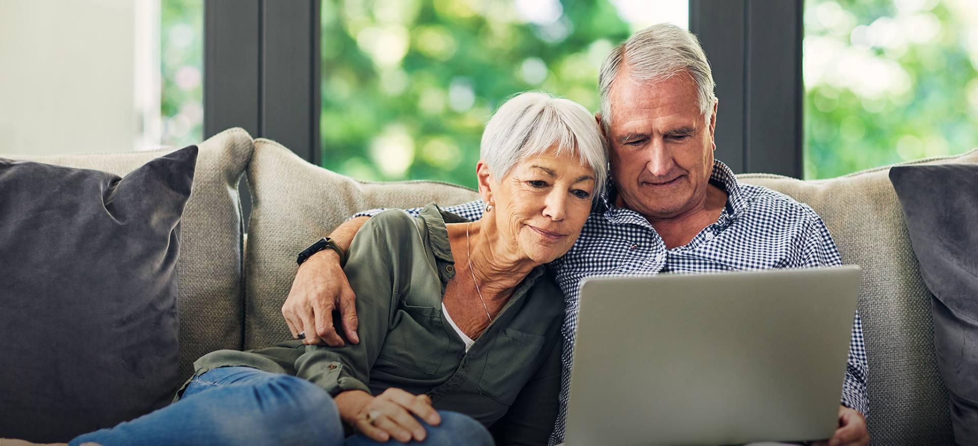Chronione ubezpieczeniem starsze małżeństwo sprawdza na komputerze informacje o polisie