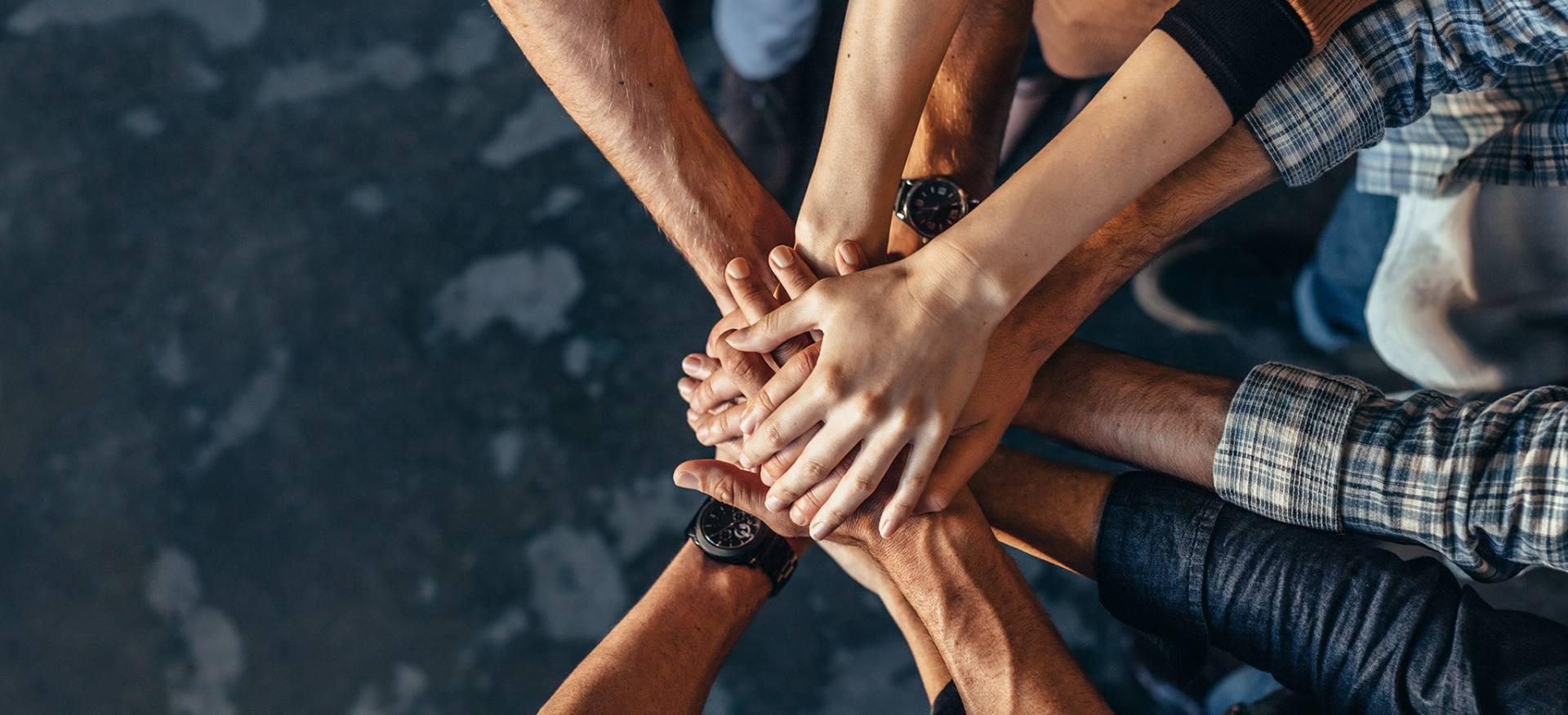 Grupa ubezpieczonych osób w geście solidarności układa dłonie jedna na drugiej