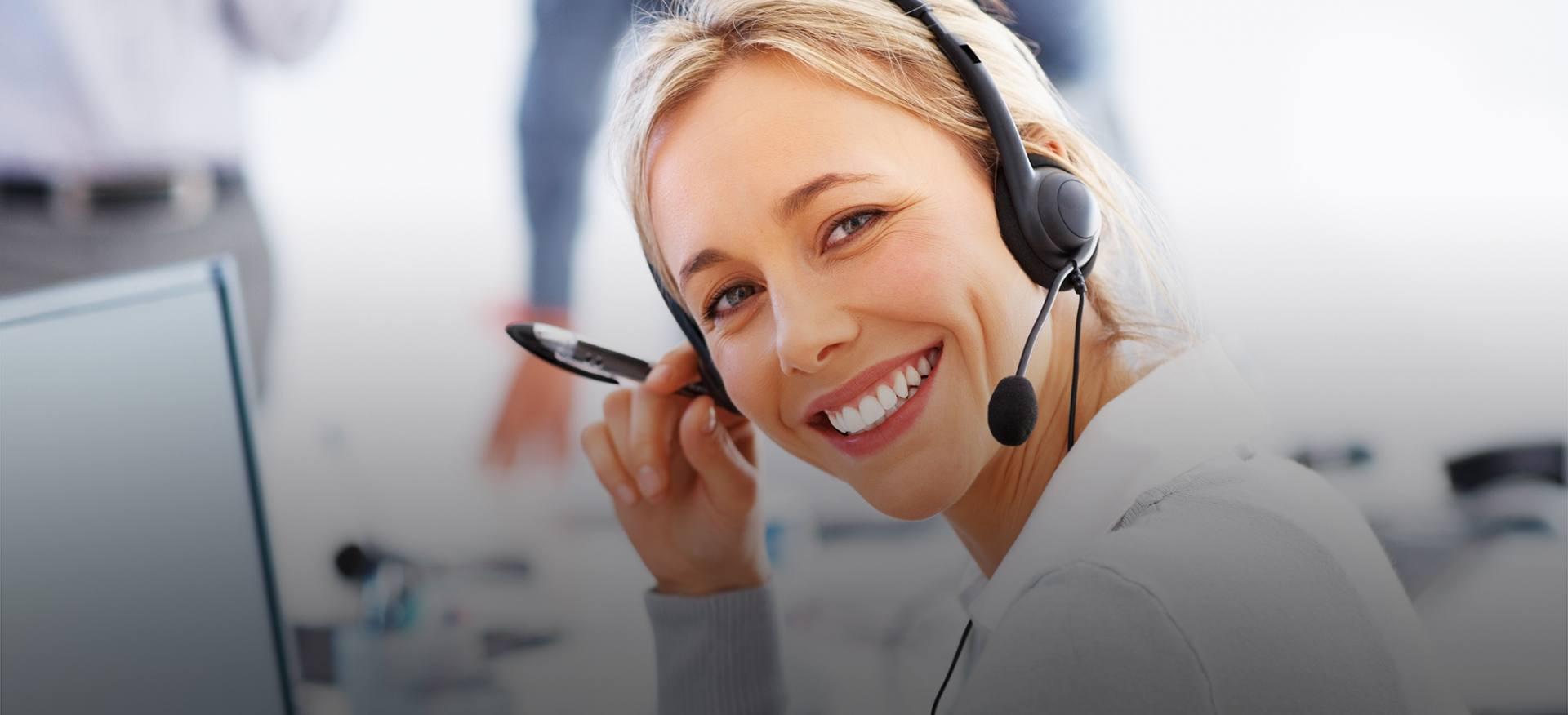 Uśmiechnięta konsultantka czeka na telefon od klienta, by odpowiedzieć na wszystkie pytania