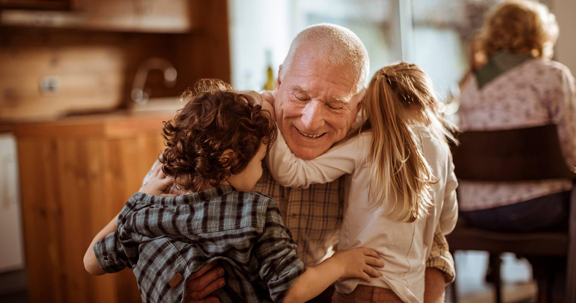 Ubezpieczony i spokojny o swoją rodzinę dziadek obejmuje dwoje wnucząt
