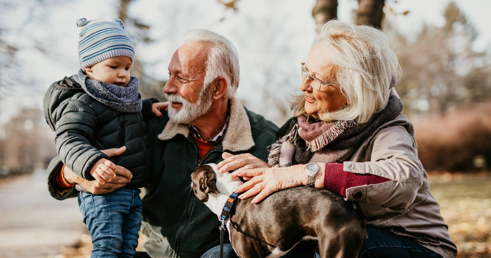 dziadkowie z wnukiem i psem na spacerze